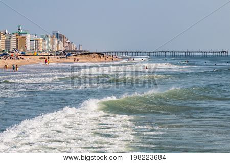 VIRGINIA BEACH, VIRGINIA - JULY 13, 2017:  Oceanfront hotels and fishing pier along the 3-mile long boardwalk and popular resort area on the Atlantic coast.