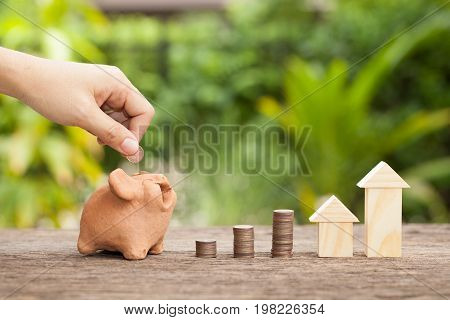 Hand's women putting golden coins in piggy bank. Concept of real estate investments Home insurance Savings plans for housing. The concept of financial savings to buy a house.