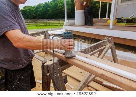 Electric Hand Held Power Fixed Base Router With Work Gloves On Wood