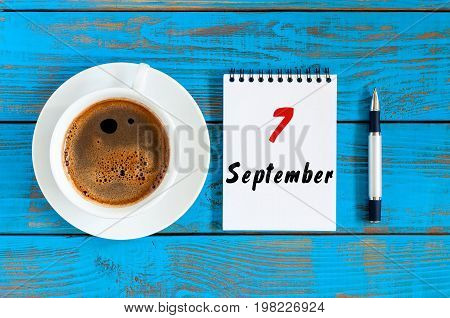 September 7th. Day 7 of month, Morning coffee cup with loose-leaf calendar on chief workplace background. Autumn time. Empty space for text.