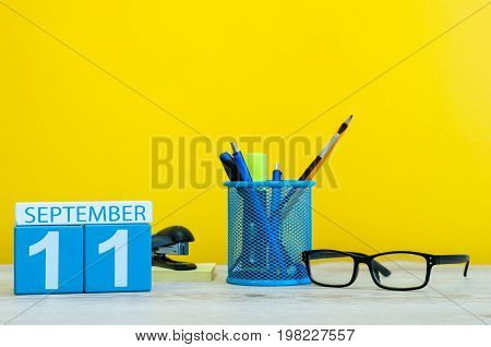 11th September. Image of september 11, calendar on yellow background with office supplies. Fall, autumn time.
