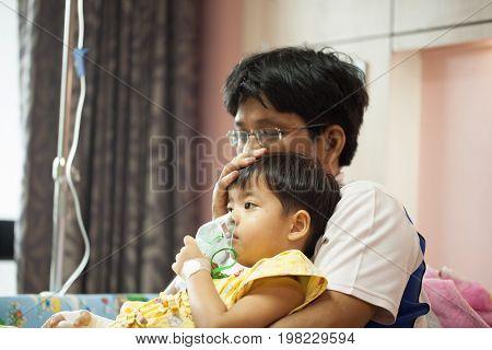 The boy wearing oxygen mask in hospital ward boy's father's lap