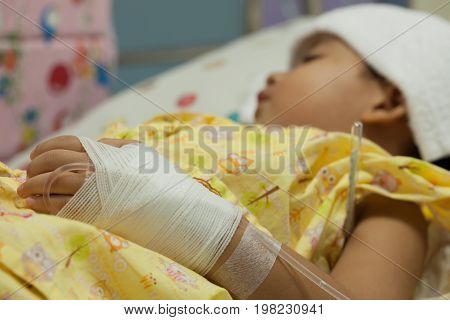 blur of a little Boy attaching intravenous tube to patient's hand in hospital bed thermometer boy hospitalized patients towel to hi fever