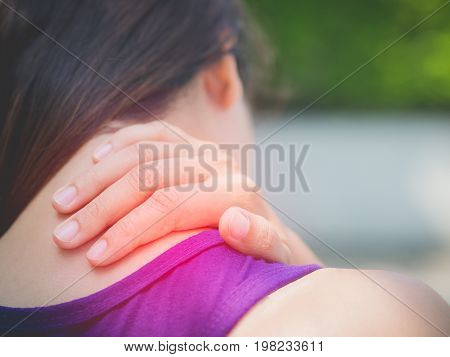 Closeup athletic young woman touching her neck by painful injury over a nature background. Sport injuries concept.