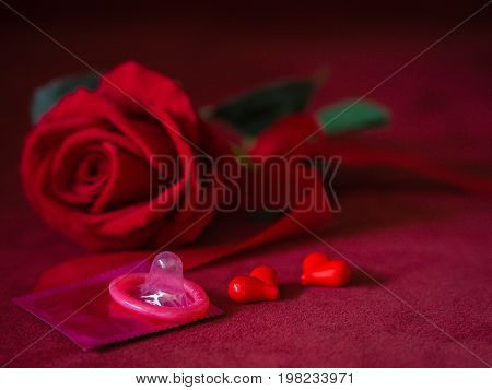 Low key of condom with red rose and hearts on pink background. Save sex Family plan and Valentine concept.
