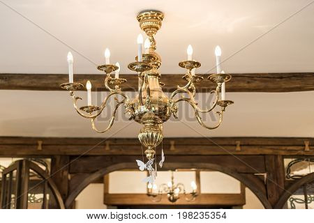 Golden chandelier with candles light and decoration in old vintage wooden room