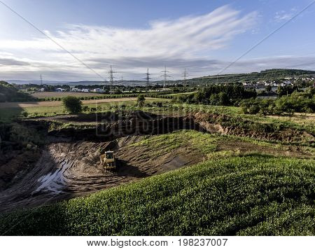 top view of heavy machine excavator bagger working in mud on construction site with green landscape surrounding