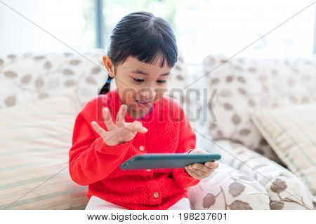 Little girl playing mobile phone at home