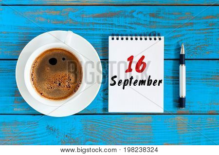 September 16th. Day 16 of month, morning chocolate cup with loose-leaf calendar on banker workplace background. Autumn time. Empty space for text.