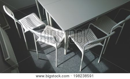The corner of a large white conference table and four chairs next to him. Close window and radiator. The concept of business meetings, training, development