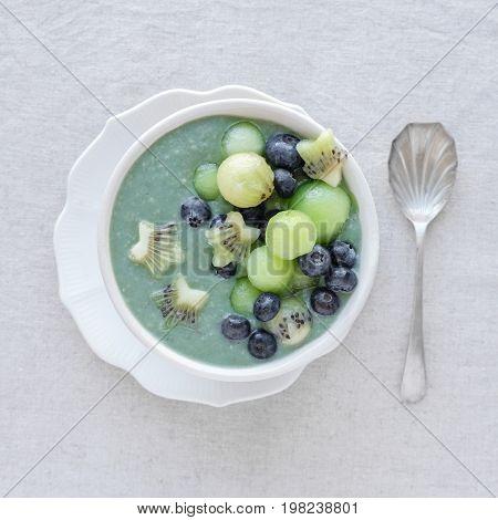 Blue Spirulina Smoothie Bowl With Melon, Kiwi Fruit And Blueberries