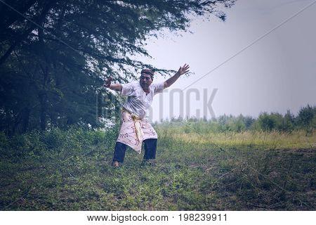 Pantai Mek Mas Kota Bahru Kelantan Malaysia. 15th July 2107 - A shot of a person wearing a traditional cloth performing a martial art Silat stance.
