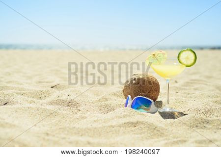 Sunglasses with cocktail glass and coconut on sand on the beach, with ocean on background. Perfect vacation.