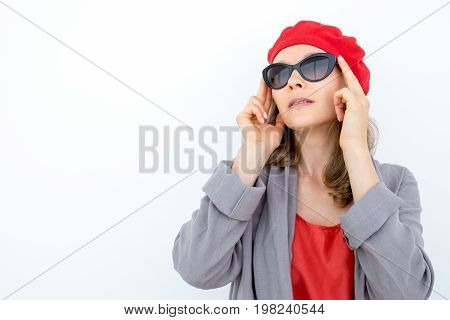 Enigmatic pensive woman in beret adjusting sunglasses and looking away. Strict French lady standing opposite white background. Elegance concept