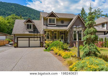 Big family house with wide driveway and garage door decorated front yard on blue sky backgrould