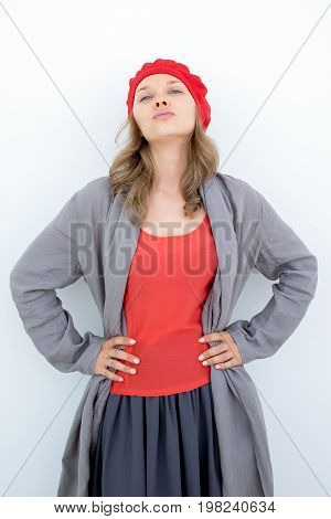 Fashionable young woman in beret posing for camera. French girl in stylish clothes puckering lips and holding hands on hips. Model concept