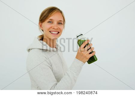 Optimistic sporty young woman maintaining balanced diet and drinking green smoothie. Cheerful content girl enjoying sport and healthy eating. Regeneration after training concept