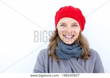 Portrait of happy attractive French woman in red beret smiling at camera. Positive young lady wearing scarf. Autumn concept