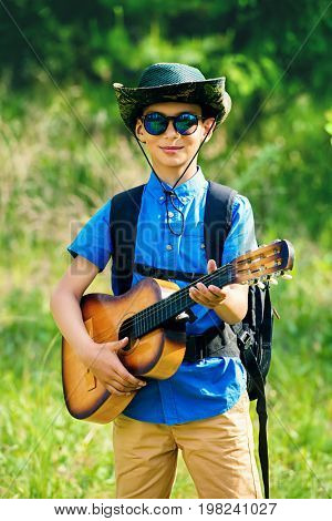 Modern ten year old boy goes hiking with a guitar and a backpack. Sunny summer holidays.