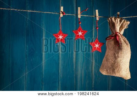 Christmas background. Christmas bag present and red stars on clothespin on deep blue wooden background with copy space. Christmas or New Year card template.