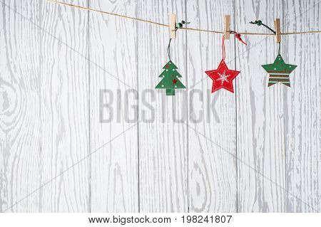 Christmas background with holiday decorations on grunge wooden board. Christmas card with red and green wooden  toys hanging on clothespin on white wooden wall. Xmas and New Year concept.