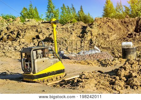 Manual ramming machine for compacting soil on construction of high-speed road around Krasnoe Selo Saint Petersburg. Light mechanized tools and equipment for works at industrial construction. Russia