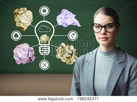 Digital composite of Woman standing next to light bulb with crumpled paper balls in front of blackboard