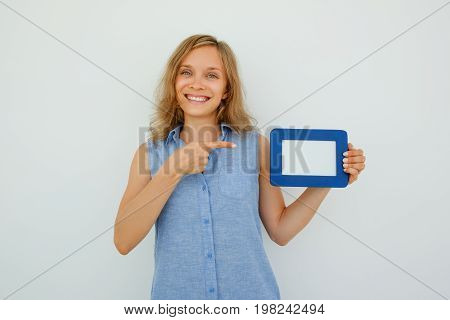 Closeup portrait of smiling young attractive woman looking at camera, holding empty picture frame and pointing at it. Isolated front view on grey background.