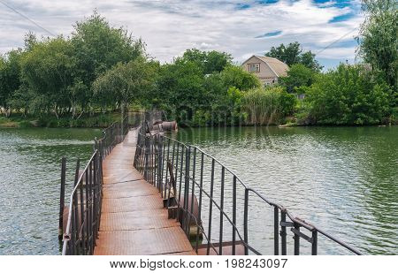 Old pedestrian pontoon-bridge over small river Schemylivka in outskirts of Dnipro city Ukraine