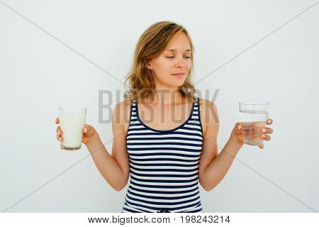 Closeup of content young attractive woman holding glass of water and glass of milk and looking at glass of water. Isolated front view on grey background.