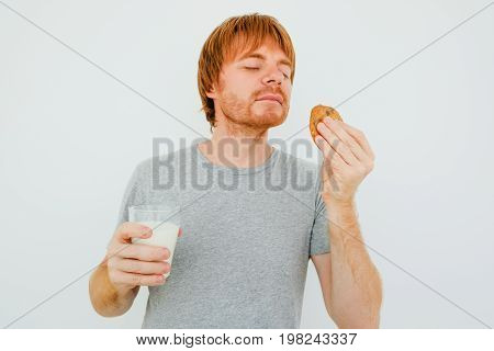 Closeup portrait of adult red-haired man holding glass of milk and smelling cookie with his eyes closed. Isolated front view on grey background.