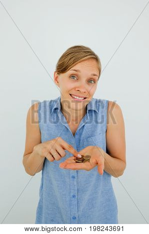 Closeup portrait of smiling young attractive woman looking at camera, shrugging and counting coins on palm. Isolated front view on grey background.