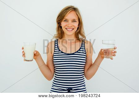 Closeup portrait of smiling young attractive woman looking at camera and holding glass of water and glass of milk. Isolated front view on grey background.