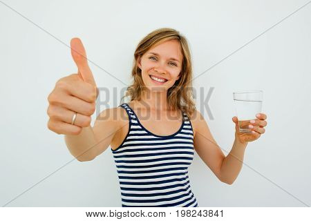 Closeup of smiling young attractive woman looking at camera, holding glass of water and showing thumb up. Isolated front view on grey background.