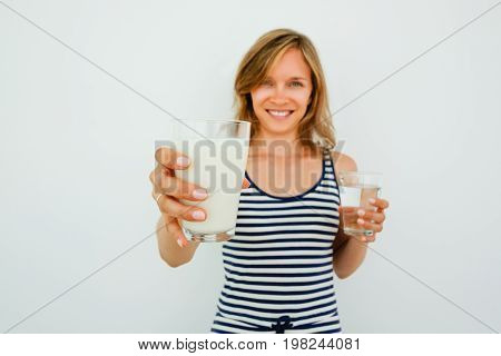 Closeup of smiling young attractive woman looking at camera, holding glass of water and offering glass of milk with focus on milk. Isolated front view on grey background.