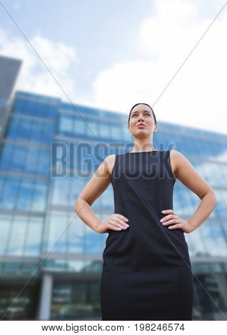 Digital composite of Business woman standing against building background