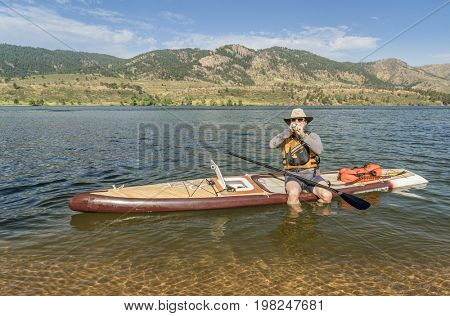 Fort Collins, CO, USA - August 2, 2017: A senior paddler eating energy food when taking a break  from paddling Starboard Expedition paddleboard with a home made hatch on Horsetooth Reservoir.