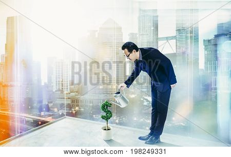 Business Man pouring water on dollar shaped tree . Business growth and entrepreneurship concept.