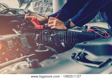 Auto mechanic checking car battery voltage repair