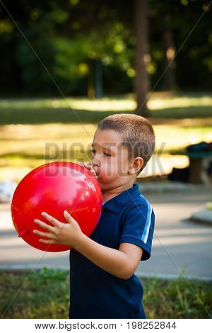 little boy inflate big red  balloon in park summer day