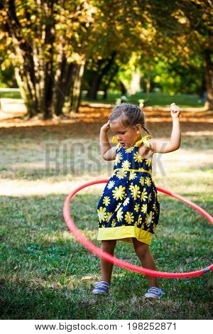 cute little girl play with hula hoop in park summer day