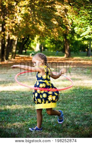 little girl play with hula hoop in park summer day