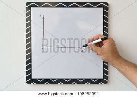 The guy is drawing a schedule on a white board. Male hand with a marker on a white board background.