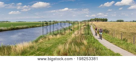 GRONINGEN, NETHERLANDS - JULY 22, 2017: Panorama of a couple riding their bicycle along the Reitdiep river in Groningen, Holland