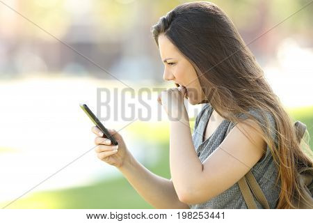 Side view of a girl angry with her mobile phone in the street