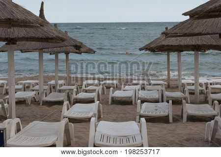 beach umbrellas empty sunbeds and lounge chairs at the beach in the romanian seaside in Neptun Constanta Romania