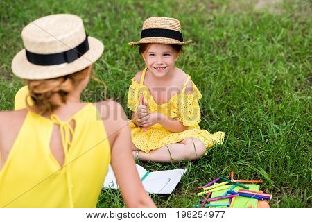 Mother And Daughter Drawing In Park