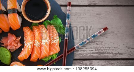 Cropped image of sushi served in plate against wood panelling