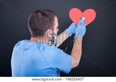 Back View Of Cardiologist Using Stethoscope On Red Shape Heart