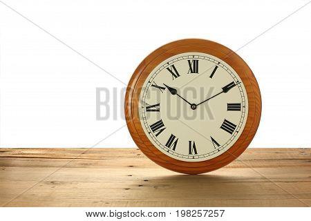 Round Mantlepiece Clock on a Wooden Background